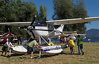 Ramp Boss Lee Cook supervises, as Certified Flight Instructor, Ray Arceneaux (far right) four Sea Scout Volunteers and Jeff Leard rotate N8516, Foothill Aviation's Cessna 182-M Skylane for parking after a flight at the Clear Lake Seaplane Splash-In, Lakeport, Lake County, California. Two Grumman Widgeons and Clear Lake and Mount Konocti are visible in the background.