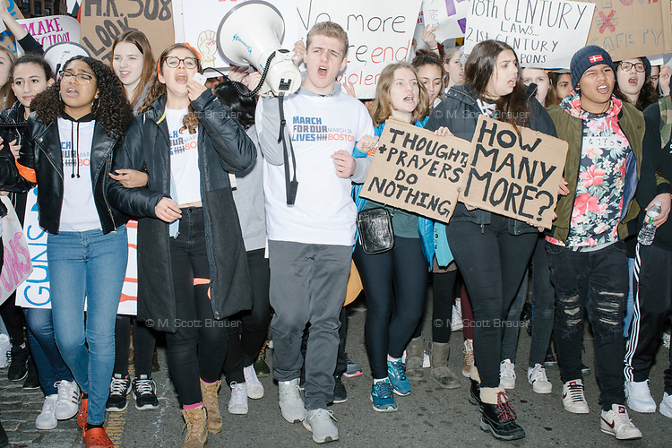 """People take part in the March For Our Lives protest, walking from Roxbury Crossing to Boston Common, in Boston, Massachusetts, USA, on Sat., March 24, 2018, in response to recent school gun violence. Here, students hold signs including """"When injustic becomes law, resistance becomes duty,"""" """"Thoughts and prayers do nothing,"""" """"How many more?"""" and others."""