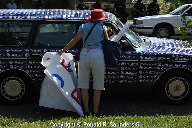 Two young women show their support for candidate Obama by covering stickers on the hood of their car during the 2008 Democratic Convention.(2)