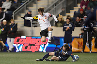 Maryland Terrapins defender Mikey Ambrose (5) jumps over Virginia Cavaliers forward Ryan Zinkhan (21) during the second half. The Maryland Terrapins defeated Virginia Cavaliers 2-1 during the semifinals of the 2013 NCAA division 1 men's soccer College Cup at PPL Park in Chester, PA, on December 13, 2013.