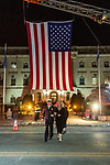 WATERBURY, CT. 20 December 2019-122019BS243 - Soon to be new Waterbury Fire Chief Terry Ballou walks under the large American flag with his wife Jennifer as they crosses the street, during the Fire Chief swearing in ceremonies at City Hall on Friday. Terry Ballou replaces former Fire Chief David Martin, who retired earlier this year. Bill Shettle Republican-American