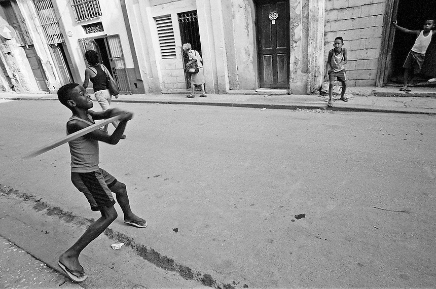 Children play baseball with a piece of lumber and a bottle cap in Old Havana, Cuba. MARK TAYLOR GALLERY