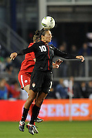 USWNT midfielder Carli Lloyd (10) heads the ball.