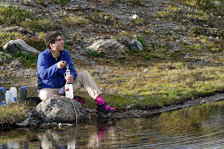 Man sitting on lake shore pumping water, near Yellow Aster Butte, North Cascades, Whatcom County, Washington, USA