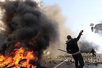 Rioters hurls paving stones beyond the barricades. Kiev, Ukraine