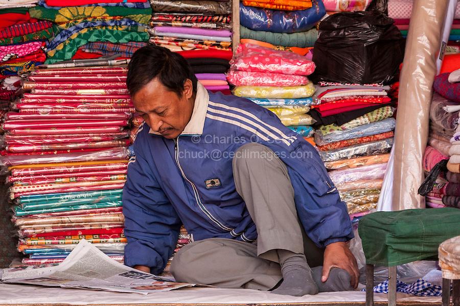 Nepal, Kathmandu.  Fabric Vendor Reading a Newspaper in his Shop.