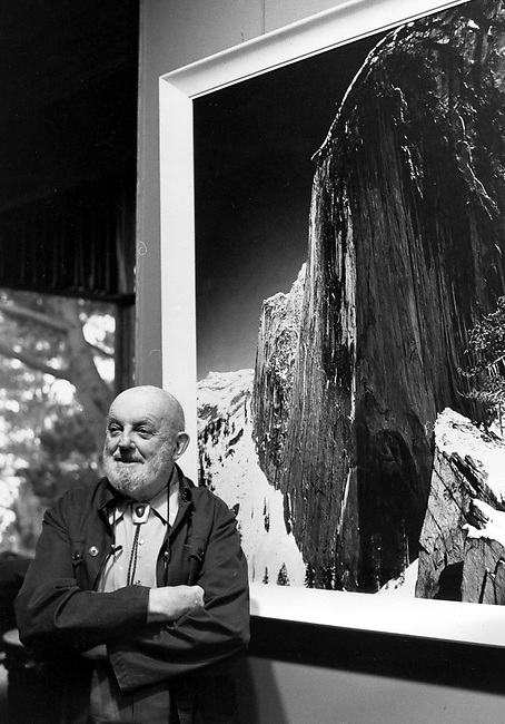 """FILE - In this Dec. 2,1980 file photo showing late photographer, Ansel Adams posing in front of his photograph of one the views of Yosemite National Park titled """"Monolith:  The Face of Half Dome, 1927,"""" in his home in Carmel Highlands, Calif.  A lawyer says a trove of old glass negatives found in Fresno have been authenticated as the work of iconic photographer Ansel Adams and are worth at least $200 million. The negatives were bought 10 years ago at a garage sale in Fresno for $45. (AP Photo/Paul Sakuma,File)"""