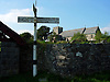 Signpost in Mid-Wales, Brecon being the nearest town. Notice the old stone wall and the stone church in the background.<br /> <br /> Stock Photo by Paddy Bergin