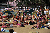 Oahu, Hawaii, USA. Tourists on Waikiki Beach with sunshades, surf boards, palm trees.