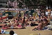 Oahu, Hawaii, USA. Tourists on Waikiki Beach with sunshades, surf boards, palm trees.