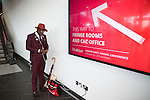 © Joel Goodman - 07973 332324 . 25/09/2016 . Liverpool , UK.  A man wearing a red hat and a maroon suit charges his phone on a wall socket at the ACC in Liverpool Docks , during the first day of the Labour Party Conference . Photo credit : Joel Goodman