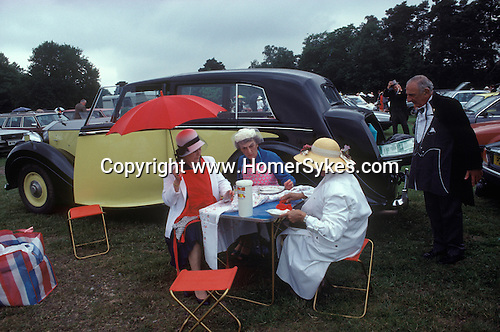 Ascot, Berkshire. 1985<br /> Mr Ivor F. Salmon proudly shows off his yellow Rolls Royce by playing butler to his wife and their guests in the Number 1 Car Park at Royal Ascot.