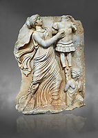 Roman SSebasteion relief  sculpture of a Goddess inscribing a trophy, Aphrodisias Museum, Aphrodisias, Turkey.  Against a grey background.<br /> <br /> A draped goddess strides forward to inscribe a military trophy to which is bound a kneeling female captive. The goddess is probably a personification such as Honour, Virtue or Courage.