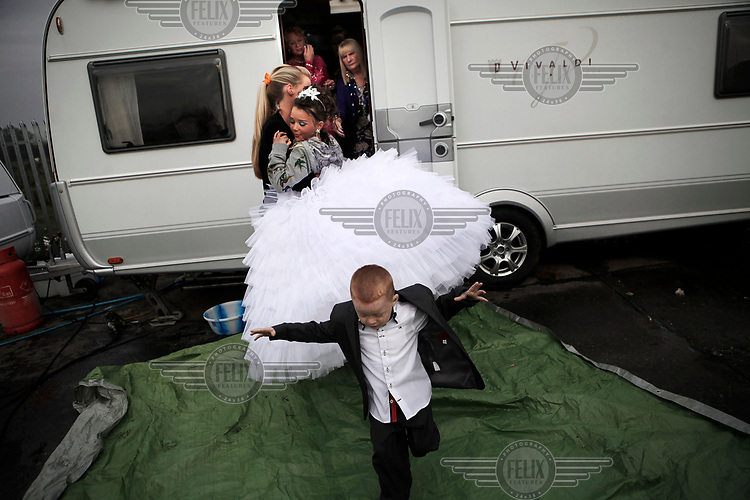 Irish Traveller Shakira Flynn is carried out of her trailer by her cousin Shirelle, as her large First Communion dress made it difficult to leave the trailer and the family did not want it to become dirty on the ground of the yards where they live.