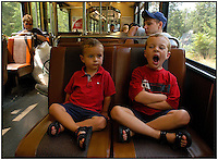 Two young brothers look tired as they ride on a light-rail train in Pennsylvania. Model released image can be used for multiple purposes. (Two boys in red and boy with blue hat are model released).