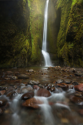 A beautiful waterfall at the end of a unique rainforest slot canyon, accessible only during low water levels in late summer.