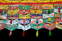 Hanging, silk-embroidered, tasseled pennants in the main hall of Ramoche Temple, Lhasa, Tibet, China.