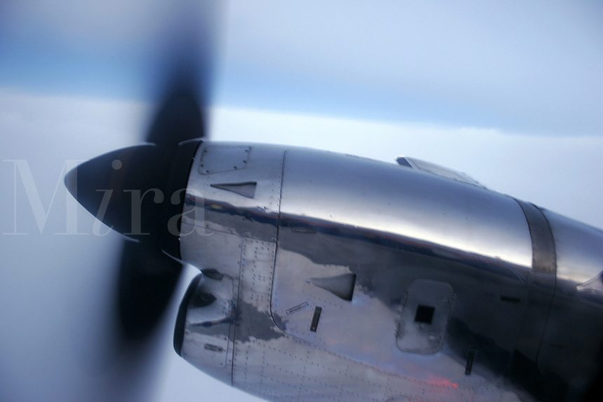 A closeup of one engine on a twin turbo prop aircraft in flight.