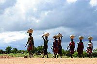 UGANDA, Karamoja, Kaabong, walking Karamojong women carry goods on the head over long distances / Karamojong Ethnie, Dorf Lochom, lokaler Transport, Frauen tragen schwere Lasten ueber lange Entfernungen