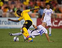 Dennis Alas (14) of El Salvador tackles the ball away from Darren Mattocks (17) of Jamaica at RFK Stadium in Washington, DC.  Jamaica defeated El Salvador, 2-0.