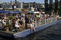 Barge serving as restaurant full of guests enjoying a summer evening out.