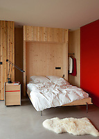 A simple double bed folds away into a pine-clad recess in this occasional guest room