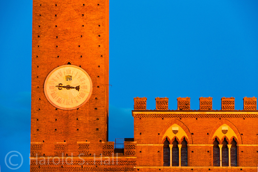 This is the bell towers in the Il Campo square, a main attraction in Siena, Italy.  People have a picnic on the brick courtyard at the base of this hundreds year old tower.