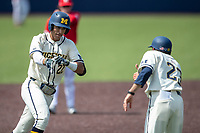 Michigan Wolverines outfielder Tito Flores (22) is greeted by third base coach Nick Schnabel (23) after hitting a home run against the Maryland Terrapins on May 23, 2021 in NCAA baseball action at Ray Fisher Stadium in Ann Arbor, Michigan. Maryland beat the Wolverines 7-3. (Andrew Woolley/Four Seam Images)