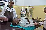Treating a machete gash in a man's hand in the ER of  Gisenyi Community Hospital in northwest Rwanda..