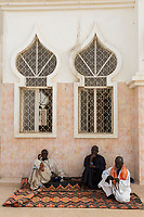 Senegal, Touba.  Three Men at Grand Mosque, One Praying with Misbaha (Subha, or Tasbih or Tasbeeha, the Muslim Rosary), One Thinking,  One Talking on Cell Phone.