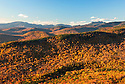 Autumn color blankets ridges of rugged terrain stretching to the horizon in this view towards the Franconia Range in New Hampshires White Mountains.