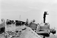 Albania. Province of Pogradec. Guri i Kug. A fisherman on top of old derelict bunkers thrown into lake Ohrid. Enver Hoxha (1908-1985) was for 40 years a dictator and a communist leader. He decided after the historic break with Russia in 1961 to protect his country from any invaders by investing in a massive fortification (more than a million bunkers were built over the years till 1985). © 2003 Didier Ruef