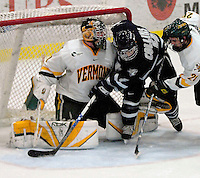 6 January 2007: University of New Hampshire defenseman Craig Switzer (4) from Peachland, BC, is checked in the crease during game action against the University of Vermont Catamounts at Gutterson Fieldhouse in Burlington, Vermont. The UNH Wildcats defeated Vermont 2-1 to sweep the two-game weekend series in front of a record setting 49th consecutive sellout at the Gut...Mandatory Photo Credit: Ed Wolfstein Photo.<br />