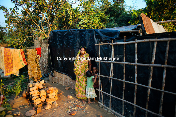 Menoka Sarkar stands with her children outside her make-shift house. Once owner to acres of land, she is now homeless with all her property gone into the river. Kulidihar village, Murshidabad District, West Bengal, India.