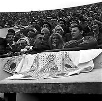 Corrida aux Arènes du Soleil d'Or (quartier des Arènes). 8 mai 1966. Scène de tauromachie. Plan rapproché des spectateurs dans les gradins (contre-plongée), au centre de la photo la chanteuse Dalida, la veste du torero est posée devant elle.