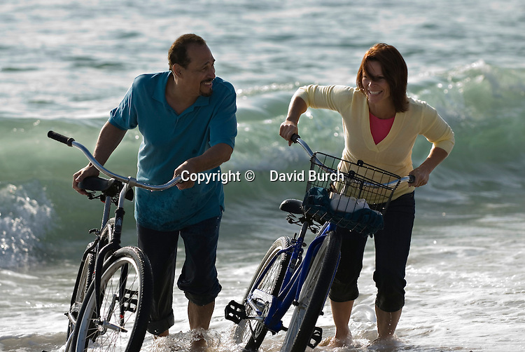 Mature couple walking with bicycles at beach, smiling