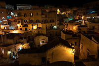 """Italy. Basilicata Region. Matera. At night, overall view on the historical centre. Known as la Città Sotterranea (""""the Underground City""""), Matera is one of the oldest continuously inhabited cities in the world, having been inhabited since the 10th millennium BC. Its historical centre """"Sassi"""", along with the Park of the Rupestrian Churches, was awarded World Heritage Site status by UNESCO since 1993. The Sassi di Matera are two districts (Sasso Caveoso and Sasso Barisano), well-known for their ancient cave dwellings.The Sassi originate from a prehistoric troglodyte settlement and are suspected to be among the first human settlements in Italy. There is evidence that people were living here as early as the year 7000 BC.The Sassi are houses dug into the calcarenite rock itself, which is characteristic of Basilicata, locally called """"tufo"""" although it is not volcanic tuff or tufa. The streets in some parts of the Sassi often run on top of other houses. The ancient town grew up on one slope of the ravine created by a river that is now a small stream. The ravine is known locally as """"la Gravina"""". In the 1950s, the government of Italy forcefully relocated most of the population of the Sassi to areas of the developing modern city. Until the late 1980s this was considered an area of poverty, since many of these houses were, and in some cases still are, uninhabitable. The current local administration, however, has become more tourism-oriented, and it has promoted the regeneration of the Sassi with the aid of the European Union, the government, UNESCO. Today there are many thriving businesses, pubs, restaurants and hotels. On 17th October 2014, Matera was declared Italian host of European Capital of Culture for 2019. Basilicata is a region in Southern Italy. 8.12.18  © 2018 Didier Ruef"""