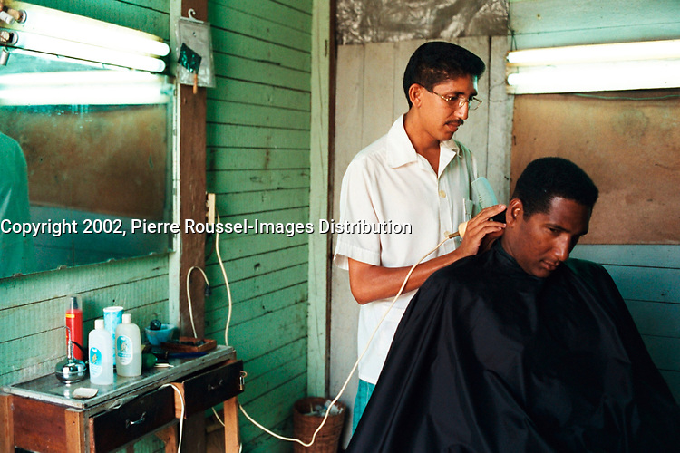 File April 27, 2002, Barracoa, Guantanamo, Cuba<br /> <br /> A Cuban man get his hairs cut by a barber in  Baracoa, Cuba.<br /> <br /> The cost of an haircut is about 10 pesos (0.40 US $) while the monthly salary is between 10 and 20 US $.<br /> <br /> Mandatory Credit: Photo by Pierre Roussel- Images Distribution. (©)2002 Copyright by Pierre Roussel <br /> ON SPEC<br /> NOTE 35mm neg scanned on Nikon LS 2000,saved in Adobe 1998 RGB.