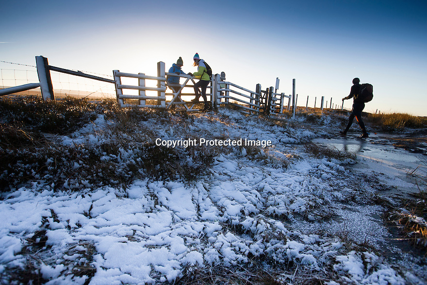 02/01/17<br /> <br /> Walkers enjoying a bracing Bank Holiday walk as they cross a snowy gateway on the Pennine Way, on Ashop Moor high above Glossop in the Derbyshire Peak District.<br /> <br /> All Rights Reserved F Stop Press Ltd. (0)1773 550665   www.fstoppress.com