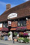 Great Britain, England, East Sussex, Battle: Tiled frontage of The Kings Head pub with colourful hanging baskets of flowers