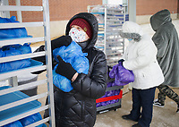 """Margie Schneider collects food bags to distribute, Saturday, February 13, 2021 at Childers-Knapp Elementary School in Springdale. Volunteers handed out about 70 bag lunches to attendees. """"We're trying to keep the community fed,"""" said Karen Smith. """"There are kids out there, and we're trying to take care of them."""" Check out nwaonline.com/210213Daily/ for today's photo gallery. <br /> (NWA Democrat-Gazette/Charlie Kaijo)"""