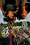 "West Friendship, Md.--8/11/04-- .Laura Gaeng, left, 14, and Jen Hopkins, 14, both of Columbia, Md., enjoy an inverted view of the Howard County Fair by way of the ""Fire Ball"" roller coaster.<br />"
