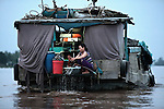 A woman does the family wash aboard a flat-bottomed boat on the Hau River in the Mekong Delta, south of Can Tho, Vietnam.  Boats such as this carry cargo throughout the region, and entire families often live aboard. Sept. 30, 2011.