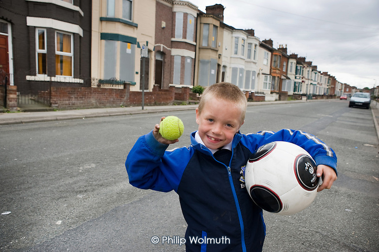 A boy plays outside his house in Anfield, close to Liverpool football stadium.  Most of the other houses in the street are boarded up and scheduled for demolition by the Merseyside NewHeartlands partnership, financed by the Housing Market Renewal Fund, part of a government strategy aimed at tackling 'low demand'.  Some long-standing residents oppose the demolition of their homes.