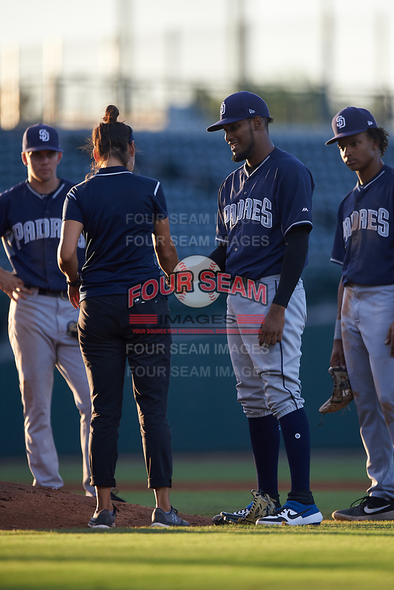 AZL Padres 1 relief pitcher Frank Lopez (17) has his wrist examined by athletic trainer Maritza Castro after fielding a line drive during an Arizona League game against the AZL Cubs 1 on July 5, 2019 at Sloan Park in Mesa, Arizona. The AZL Cubs 1 defeated the AZL Padres 1 9-3. (Zachary Lucy/Four Seam Images)