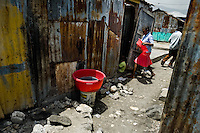 A Haitian woman enters a shack in the slum of Cité Soleil, Port-au-Prince, Haiti, 24 July 2008. Cité Soleil is considered one of the worst slums in the Americas, most of its 300.000 residents live in extreme poverty. Children and single mothers predominate in the population. Social and living conditions in the slum are a human tragedy. There is no running water, no sewers and no electricity. Public services virtually do not exist - there are no stores, no hospitals or schools, no urban infrastructure. In spite of this fact, a rent must be payed even in all shacks made from rusty metal sheets. Infectious diseases are widely spread as garbage disposal does not exist in Cité Soleil. Violence is common, armed gangs operate throughout the slum.