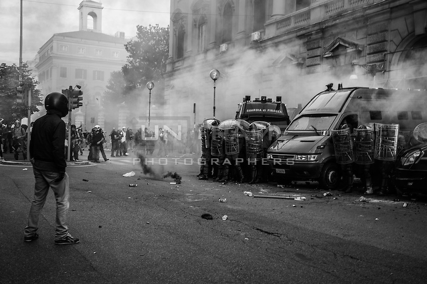 A rioter wearing a helmet faces Guardia di Finanza police in riot gear defending the entrance of the Ministry of Economy.  Rome, Italy. 09/10/2013