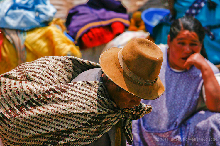 A Peruvian man carries his purchases at the Pisca market.