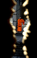 Images from the Book Journey Through Colour and Time,view through the railings/decor inside the Angkor Wat Temple Siam Reap Cambodia, a lone Buddhist Monk.