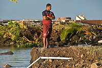 A young man from Poutasi village, who lost family members, surveys the damage 24 hours after the tsunami. More than 170 people died when a tsunami triggered by an 8.3 magnitude earthquake hit Samoa and neighbouring Pacific islands on 29/09/2009. Samoa (formerly known as Western Samoa)..